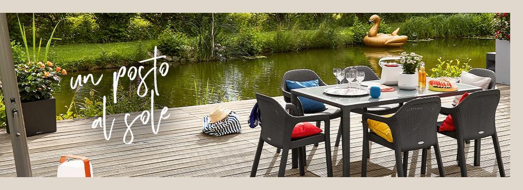 Il tavolo da giardino LECHUZA coperto con sedie in granito sorge su un pontile in legno vicino a un lago. Sulle sedie giacciono cuscini colorati.