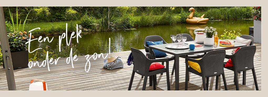 Gedekte LECHUZA tuintafel met stoelen in graniet staat op een houten steiger aan een meer. Op de stoelen liggen kleurrijke zitkussens