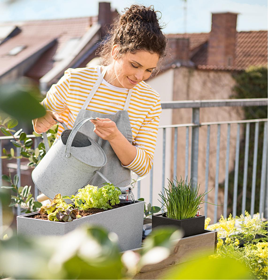 A woman waters her planted salad
