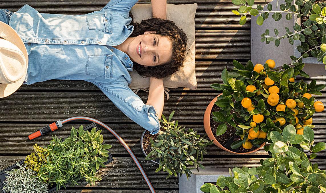 Mujer tumbada en la terraza entre las macetas de LECHUZA