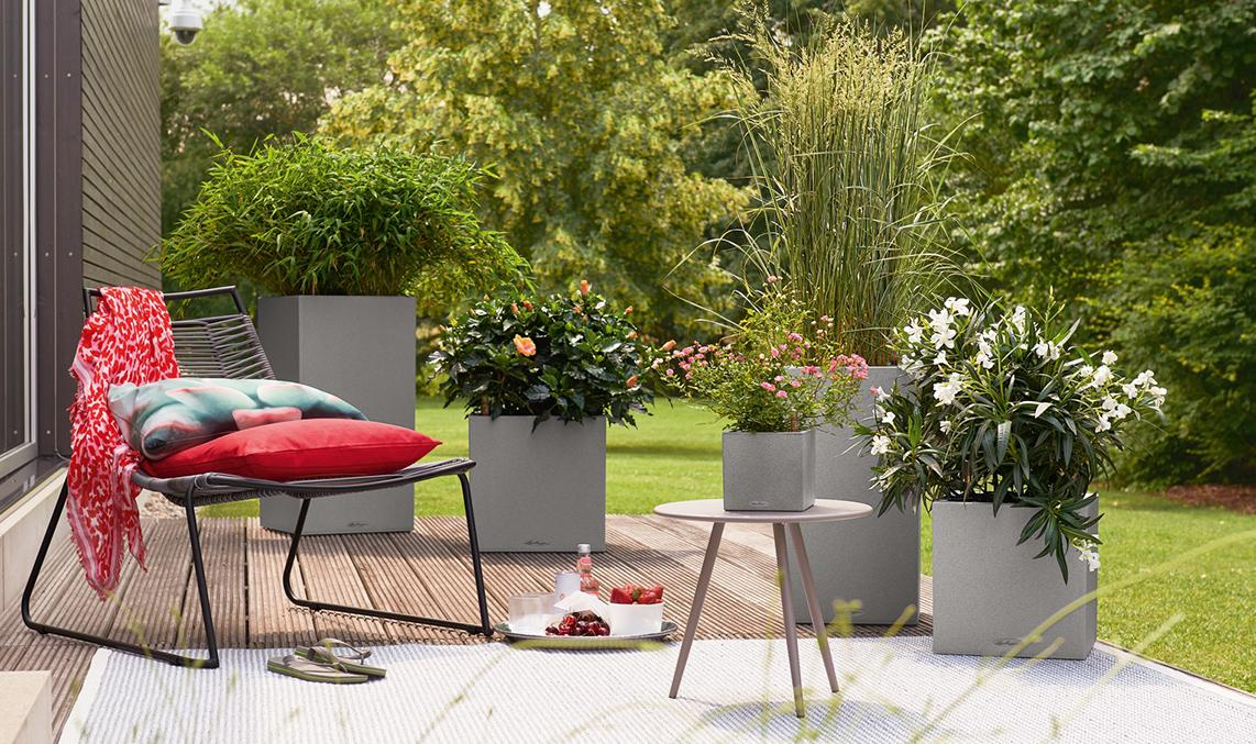 Several planters from the LECHUZA Stone Collection are planted on a terrace