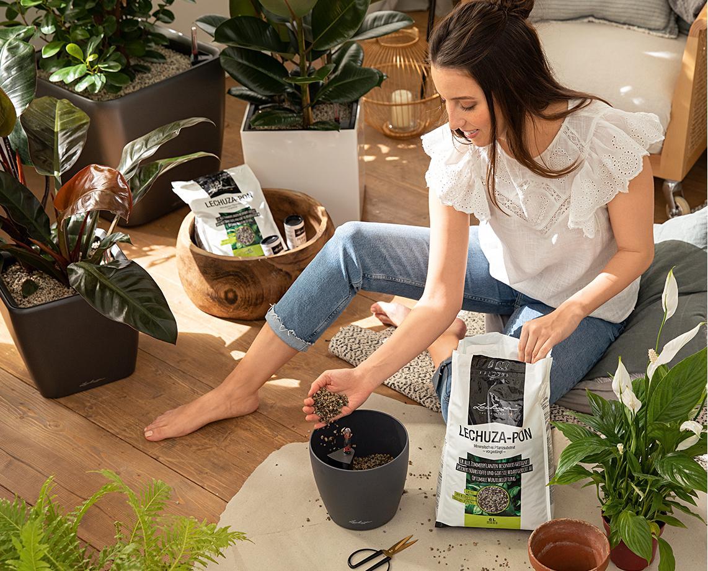 Eine junge Frau befüllt ein Pflanzgefäß mit LECHUZA-PON