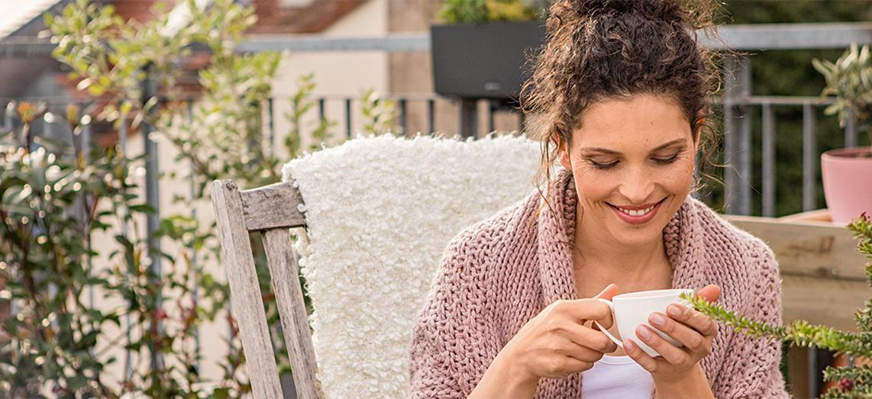 Frau sitzt auf Terrasse und trinkt Tee