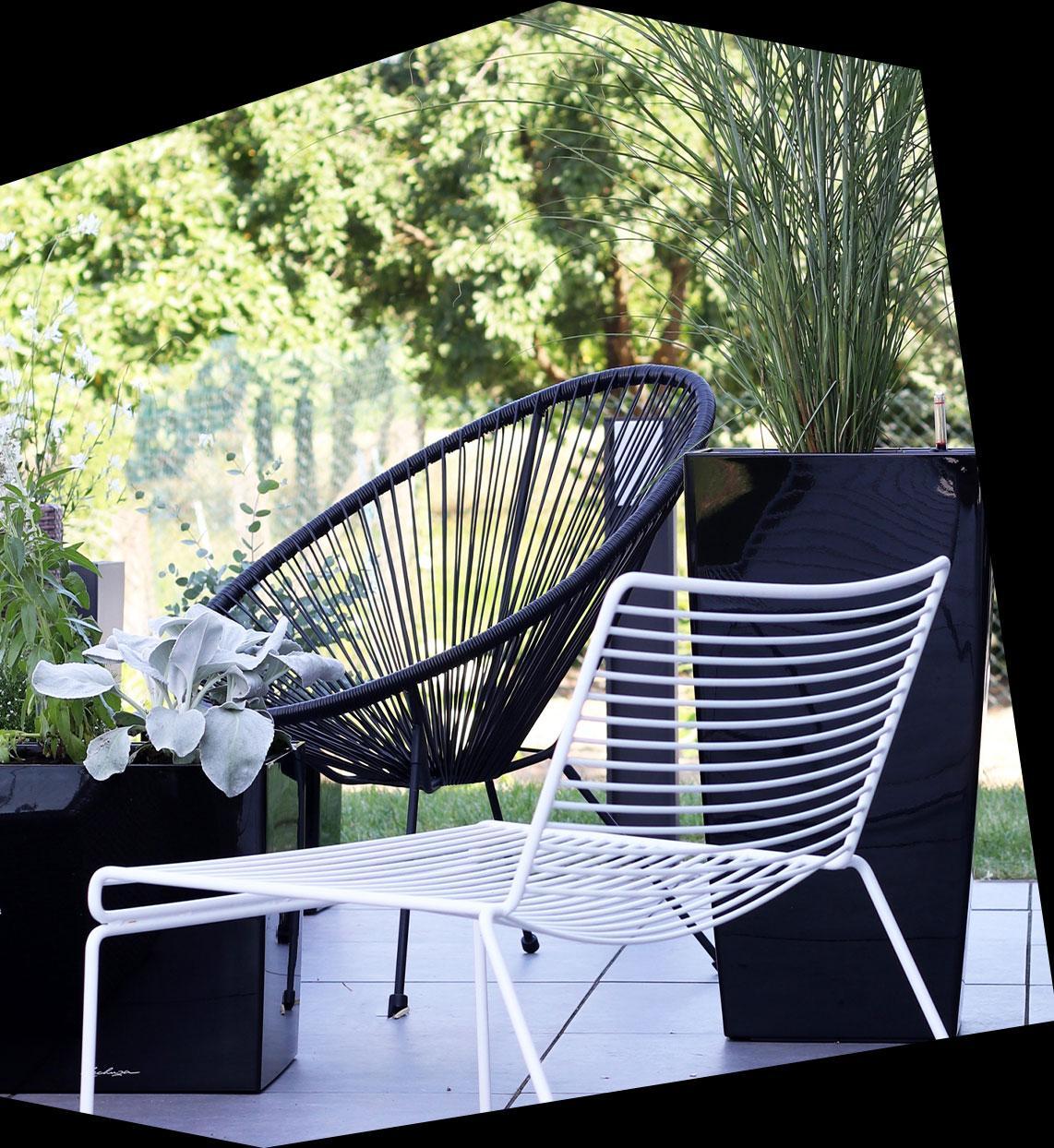 Zwarte hoogglans plantenbak CUBICO en CUBE op een terras met zwart-witte stalen buismeubels.