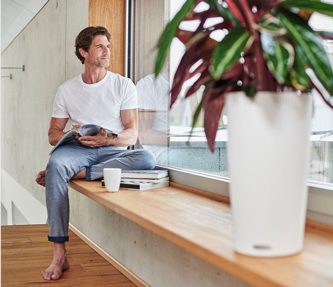 'De mens zit ontspannen op een brede vensterbank