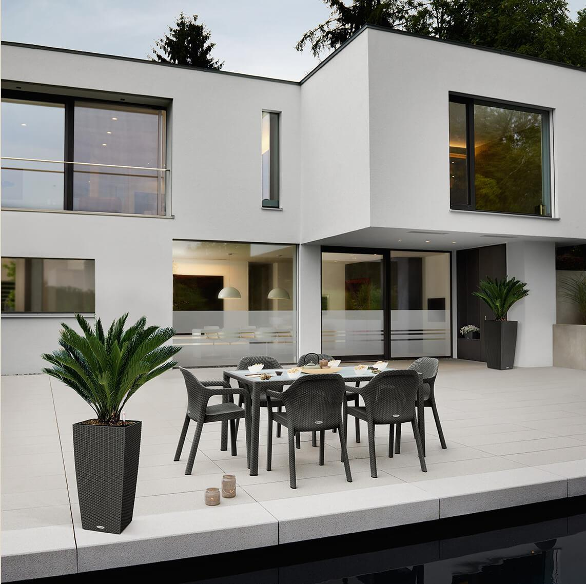Modern Bauhaus villa at dusk. On the terrace in front of the villa there is a LECHUZA 7-seater suite in the colour granite
