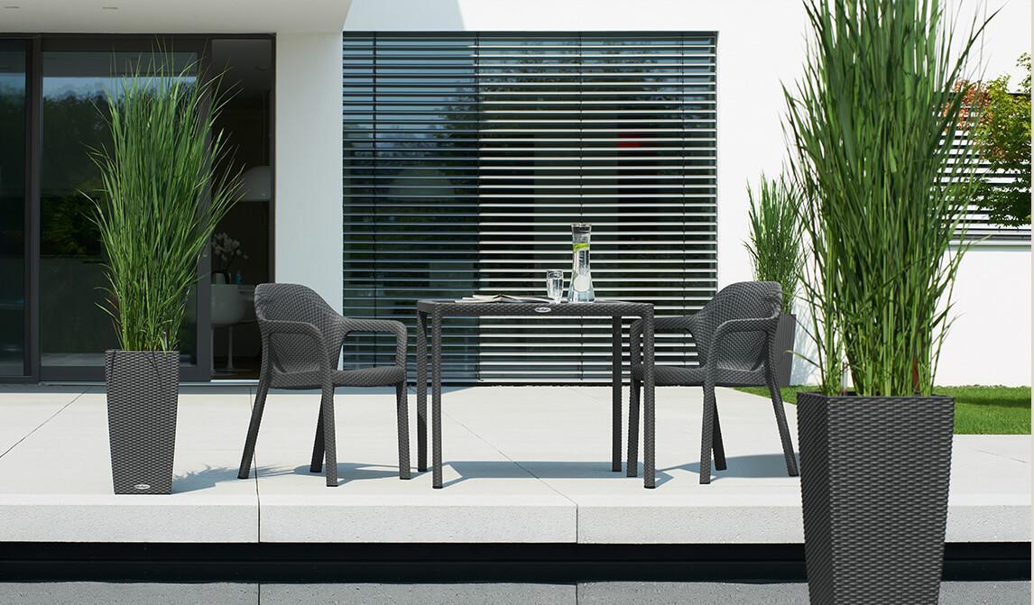 Ένα τραπέζι κήπου και δύο καρέκλες LECHUZA σε μία μοντέρνα βεράντα με όμορφα φυτά.