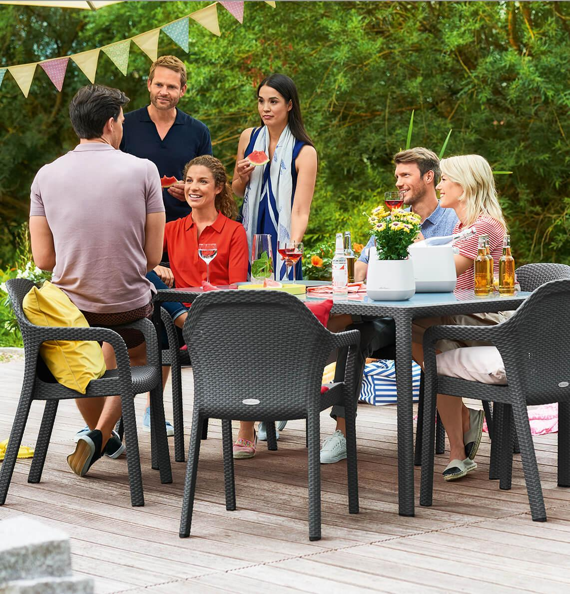 Freunde feiern eine Party im Garten und sitzen gemütlich an einem Tisch