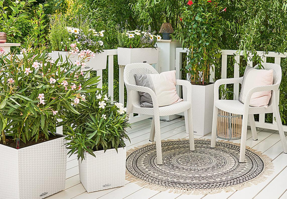 'Twee witte LECHUZA stapelstoelen op een romantisch landhuisterras. Daarnaast LECHUZA Cottage plantenbakken