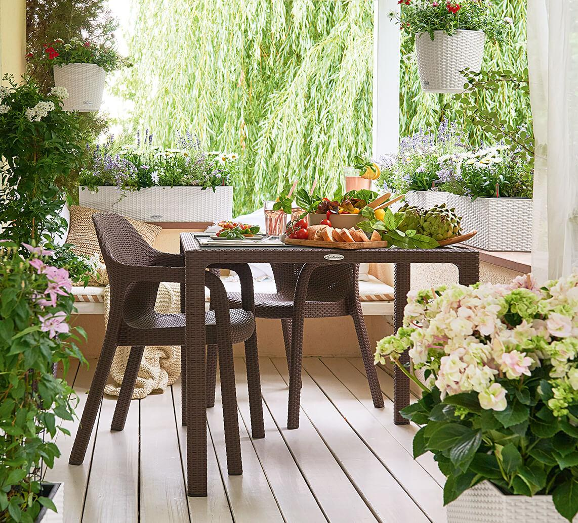 On a covered country veranda there is a beautifully set LECHUZA garden table with two chairs. It is surrounded by various LECHUZA planters in wickerwork look which are planted with various flowers e.g. hydrangeas and orleander.