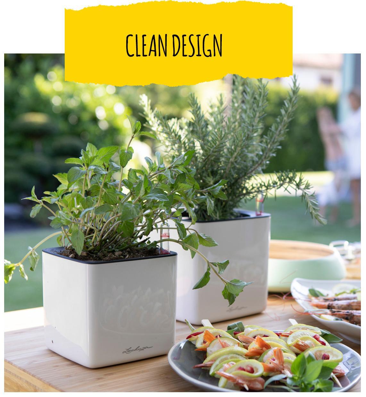 Twee LECHUZA CUBE Glossy in wit staan in de buitenkeuken. Ze zijn met verschillende kruiden beplant.
