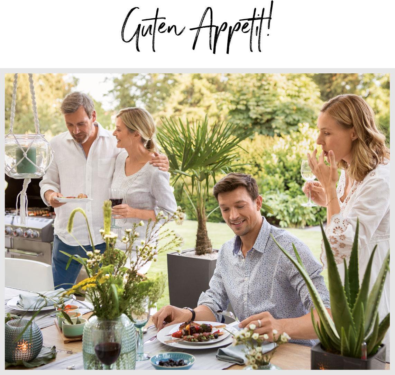 Vier Freunde setzen sich zum Essen an einen schön gedeckten Tisch im Freien