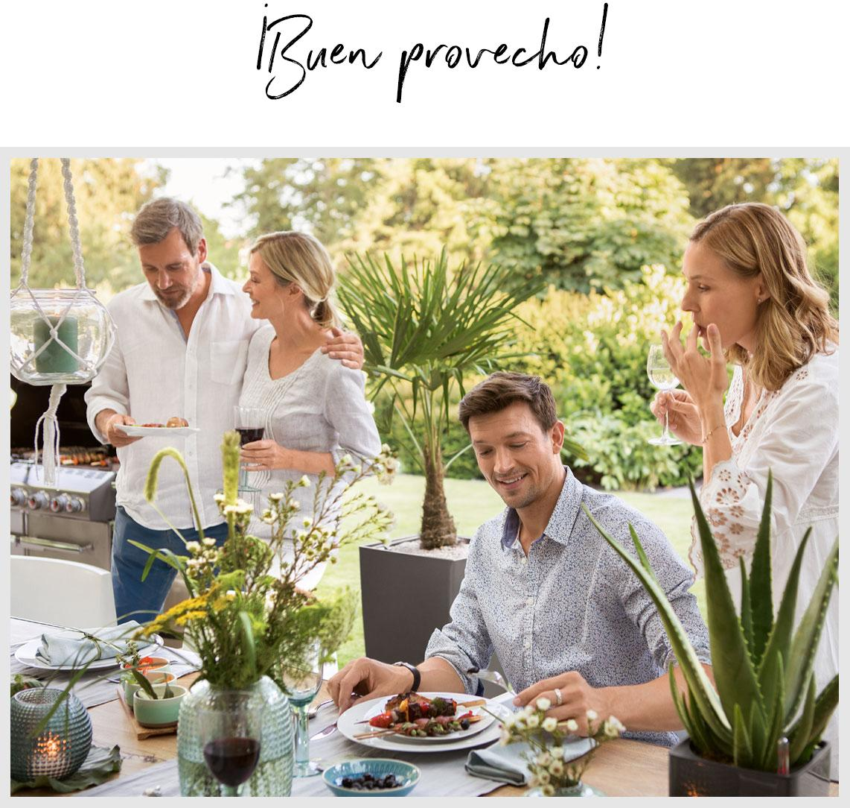 Cuatro amigos se sientan para comer en una mesa bien puesta al aire libre.