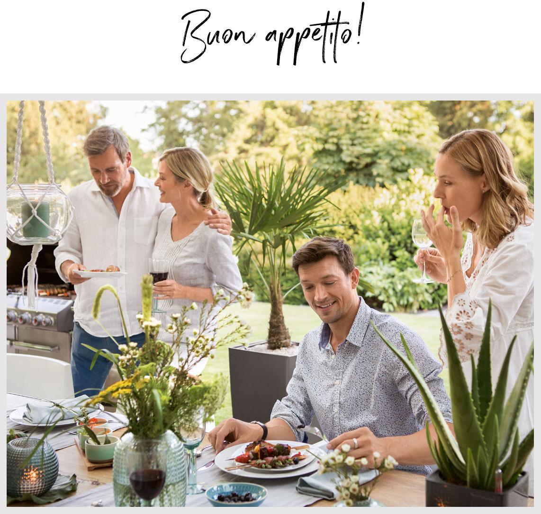 Quattro amici si siedono a cena ad un tavolo splendidamente apparecchiato all'aperto.