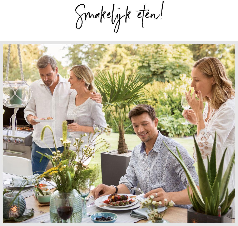 Vier vrienden gaan zitten om te eten aan een mooi gedekte tafel buiten.