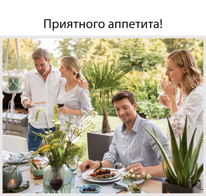 Четверо друзей садятся обедать за красиво накрытый стол на свежем воздухе.