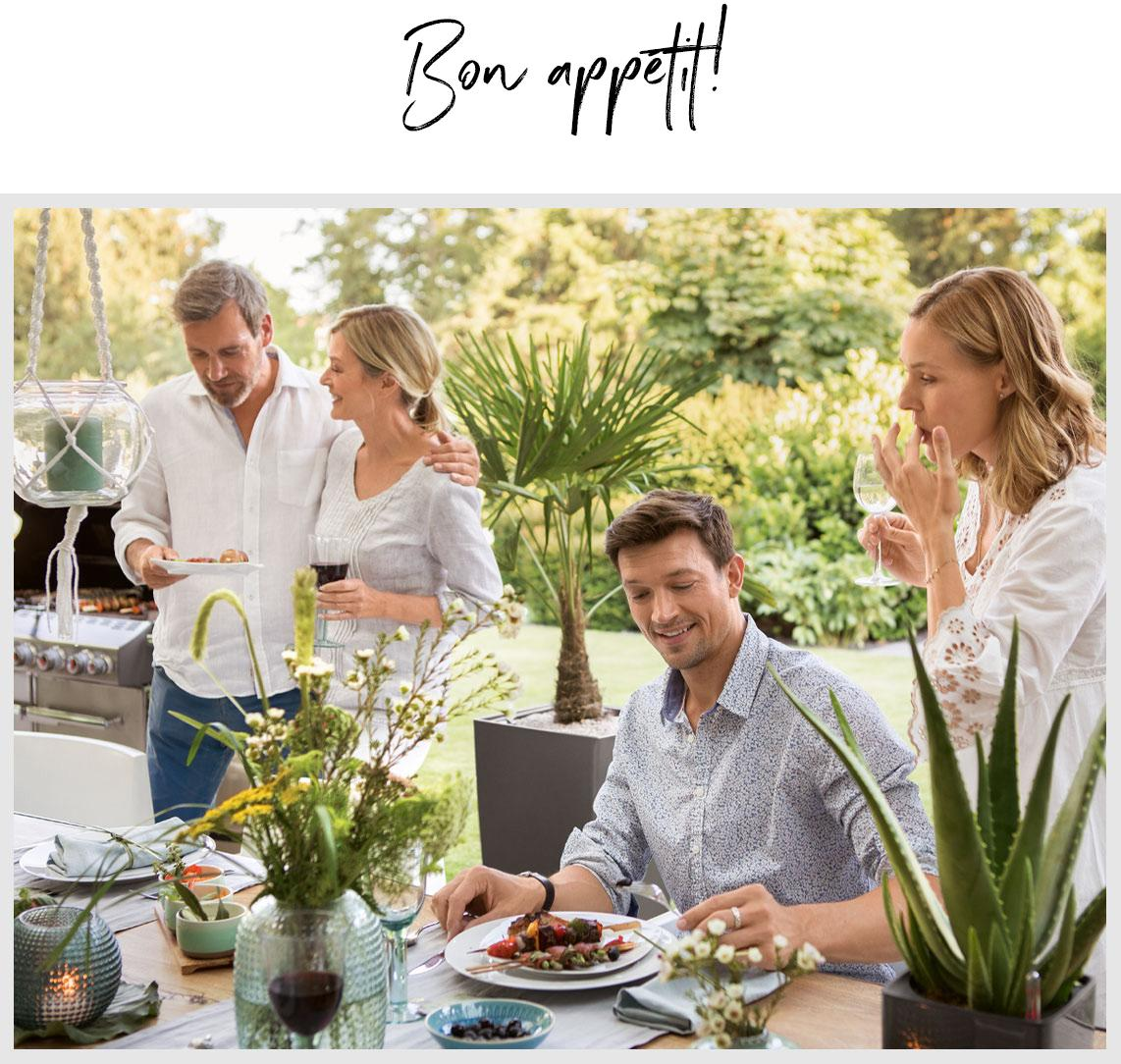Four friends sit down to dinner at a beautifully laid table outdoors.