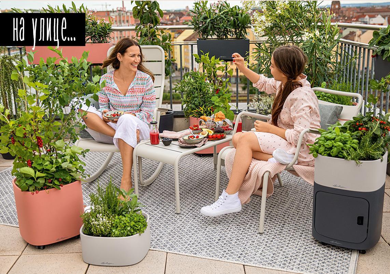 Мать и дочь сидят на балконе и перекусывают ягодами