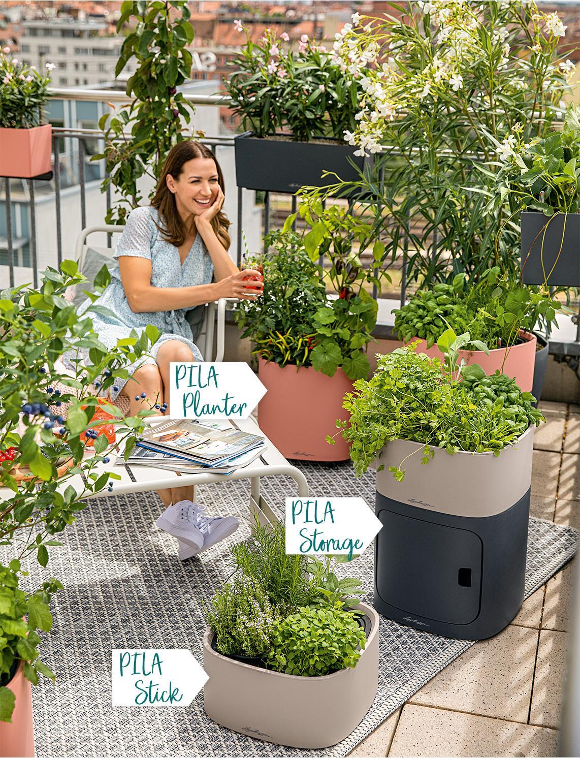 Mutter und Tochter sitzen auf Balkon mit bepflanzten PILA Pflanzgefäßen