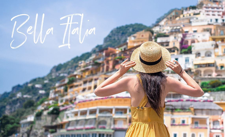 Una mujer joven con un sombrero de paja y un vestido amarillo con el pueblo de Positano (en la Costa Amalfi) de fondo