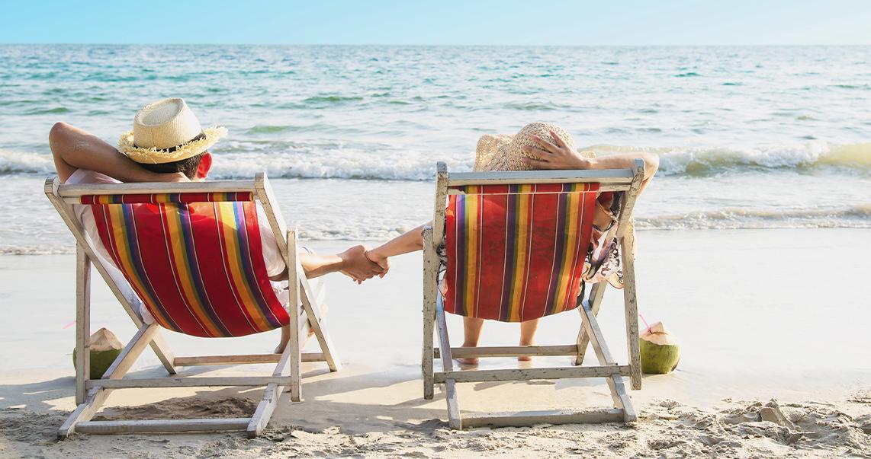 Entspanntes Paar liegt am Strand auf Liegestühlen und hält sich an der Hand